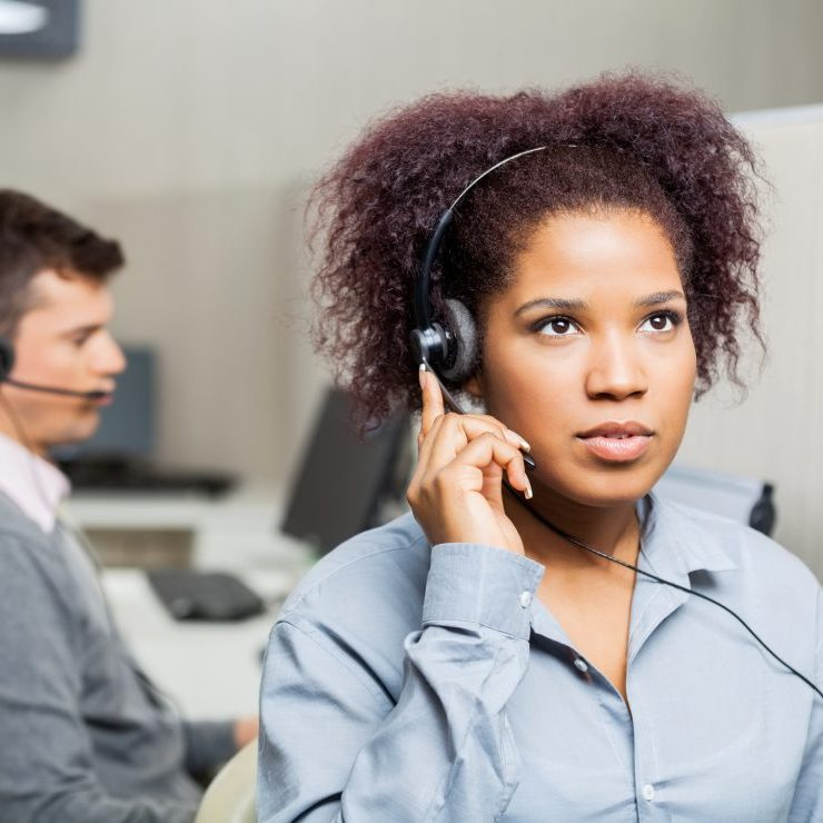 Serious female customer service representative using headset with male colleague in background at office